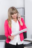 Woman is phoning and looking at a calendar Royalty Free Stock Photos