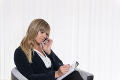Woman is phoning and making notes Royalty Free Stock Image