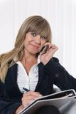 Woman is phoning and making notes Royalty Free Stock Photos