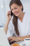 Woman phoning and using her laptop Royalty Free Stock Photography