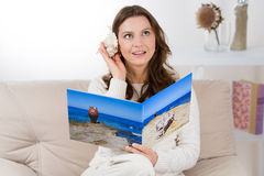 Woman with photo book listening a seashell Royalty Free Stock Photography