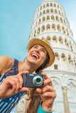 Woman with photo camera in front of tower of pisa Stock Images
