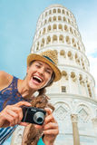 Woman with photo camera in front of tower of pisa Stock Image