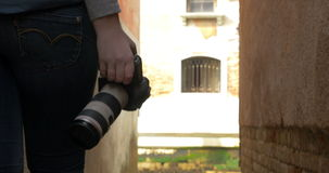 Woman with photo camera wandering in alleyway. Steadicam shot of a woman photographer walking in narrow alleyway with professional photo camera in hands. She stock video