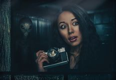 Woman and alien. Woman with photocamera and alien behind her Royalty Free Stock Images
