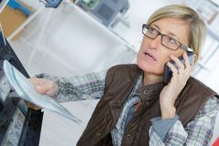 Woman by photocopier holding instructions booklet and talking on telephone. Woman Stock Photos