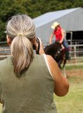 Woman Photograher. Woman photographing horse and rider Royalty Free Stock Image