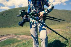 Woman photograher with tripod and digital camera in hands. Walking on mountain royalty free stock photo