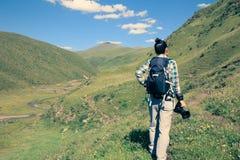 Woman traveler taking photo on mountain. Woman photograher walking on mountain with camera stock photo