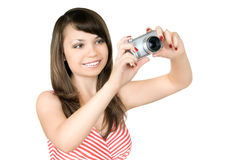 Woman the photographer. The young woman the photographer presses the button of the camera, smiles, on a white background, is isolated Stock Photos