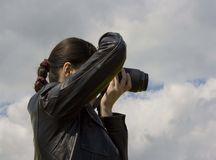 Woman photographer. In leather jacket Royalty Free Stock Photography
