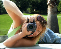 Woman photographer. Lying down on golf course, taking a picture Royalty Free Stock Photography