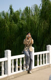 Woman photographer. Woman, possibly a tourist, taking a photo while sitting on a fence Royalty Free Stock Image