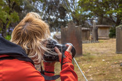 Travel Photographer. Woman holding her camera up to take a photo in an ancient cemetery a Port Arthurt in the Island of the Dead, Tasmania, Australia Royalty Free Stock Images