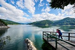 Woman photographer with blue backpack on lake Vidraru Carpathians Romania Royalty Free Stock Images