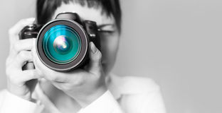 Woman photographer with camera. Pretty woman is a professional photographer with dslr camera Royalty Free Stock Photo
