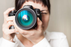 Woman photographer with camera. Pretty woman is a professional photographer with dslr camera Stock Photos