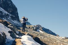 A woman photographer with camera and backpack in a winter jacket with fur stands on the snow mountain in Switzerland.  Fluela pass Royalty Free Stock Images