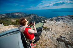 Woman photographer with car on the top of mountain Stock Images