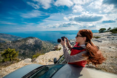 Woman photographer with car on the top of mountain Stock Photo
