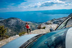 Woman photographer with car on the top of mountain Royalty Free Stock Photo