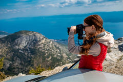 Woman photographer with car on the top of mountain Royalty Free Stock Images
