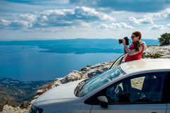 Woman photographer with car on the top of mountain Royalty Free Stock Photos