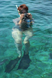 Woman photographer diving into water of Red sea. A Woman photographer diving into water of Red sea Stock Image