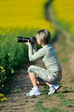 Woman photographer on field in summer Royalty Free Stock Photography