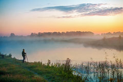 Woman photographer at a foggy lake. Woman photographing a misty lake at sunrise Stock Image