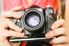 Woman photographer holding 35mm film camera. Royalty Free Stock Photos