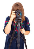 Woman photographer looking into the camera lens on a tripod Stock Photography