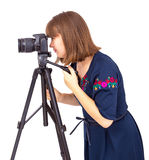 Woman photographer looking into the camera lens on a tripod Royalty Free Stock Photos