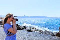 Woman photographer Nature photographer shooting the sea. Travel Concept royalty free stock image