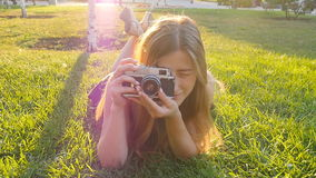 Woman the photographer with old camera lays on a grass stock video