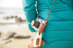 Woman photographer with  old camera on the ocean. View from the back. Close-up Royalty Free Stock Photography