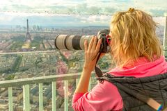 Woman photographer in Paris. Traveler photographer takes photos of Tour Eiffel from observation deck of Tour Montparnasse. Woman photographer in French capital Stock Photo