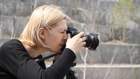 Woman photographer photographs in an abandoned marble quarry.  stock video footage