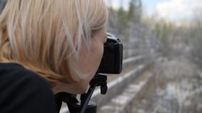 Woman photographer photographs in an abandoned marble quarry.  stock video