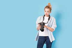 Woman photographer is satisfied about her work. Model isolated on a blue background with copy space Royalty Free Stock Images