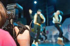 Woman photographer shooting  dancers group. Photographer shooting  dancers group on stage Royalty Free Stock Photos
