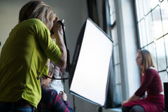 Woman photographer in a studio making portrait stock photography