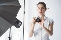 Woman photographer in studio setting camera Stock Image
