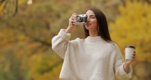 Woman photographer take a photo walking in the autumn forest. Enjoys day with coffee stock video footage