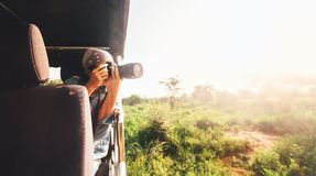Woman photographer takes a picture with professional camera from stock photography