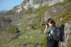 Woman photographer taking photo in the countryside Stock Images