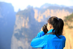 Woman photographer taking photo mountain peak Royalty Free Stock Images