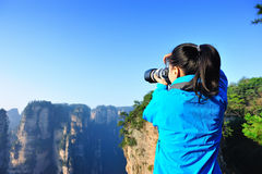 Woman photographer taking photo mountain peak Stock Photo