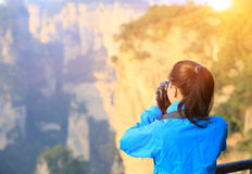 Woman photographer taking photo mountain peak Royalty Free Stock Image