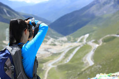 Woman photographer taking photo at plateau mountain peak in tibet,china Royalty Free Stock Images